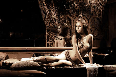 Topless brunette beauty on lounge
