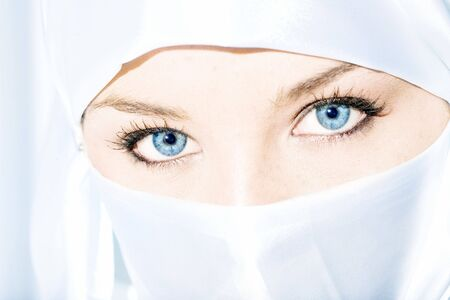 Blue eyed girl wearing face veil Imagens