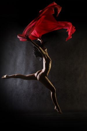 Nude model in studio dancing with red cloth