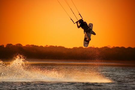 Kite boarder realizar un salto a la puesta del sol  Foto de archivo