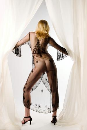 Una mujer rubia en lencer�a pura est� entre cortinas