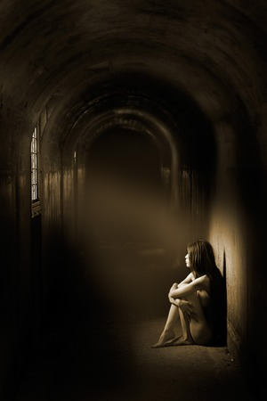 A beam of light shines onto a woman Imagens