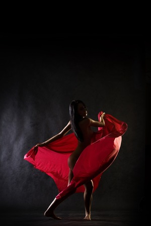 young naked girl:  model in studio dancing with red cloth