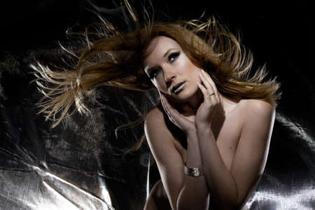 High fashion image of woman with sheer silver cloth photo