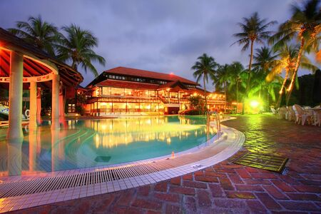 Beautiful resort pool and restaurant by evening photo