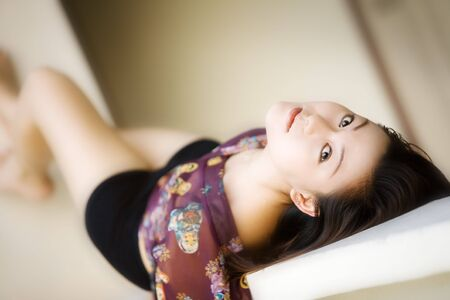 lays: Beautiful Asian woman lays on her back looking at camera Stock Photo