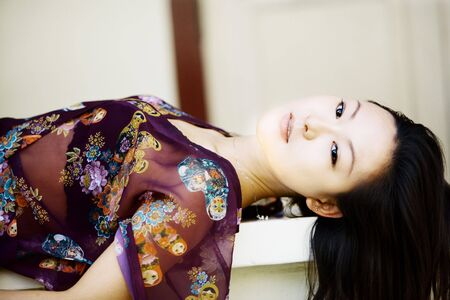 lays: Beautiful Asian woman lays on her back looking away Stock Photo