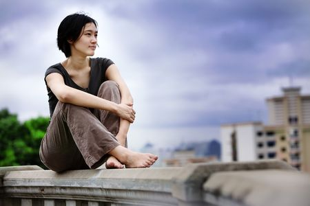 overlooking: Asian girls sits at lookout overlooking city