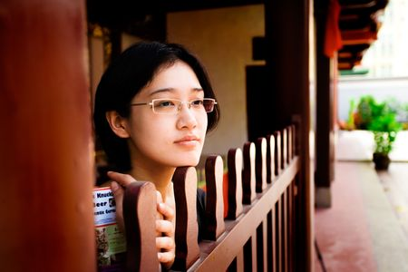 studious: Studious Asian girl looks peacefully off into the distance Stock Photo
