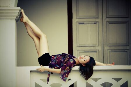 lays: Pretty Asian girl lays on balustrade with legs up