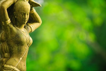 Statue of Asian woman against green foliage background Stock Photo
