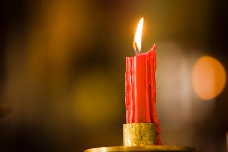 One solitary red candle on a warm out of focus background