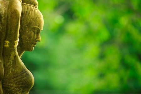 jungle girl: Statue of Asian woman against green foliage background Stock Photo