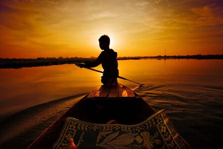 Silhouette of boy paddling boat at sunset photo