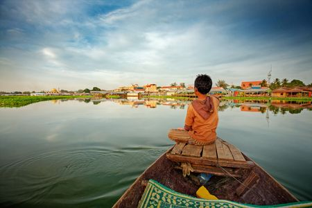 prow: Cambodian boy on prow of small boat overlooking lake
