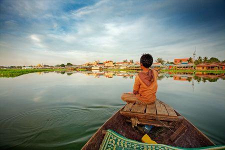 Cambodjaanse jongen op voorsteven van kleine boot met uitzicht op het meer Stockfoto