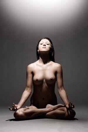 Naked woman meditates on gray studio background Stock Photo - 2549220