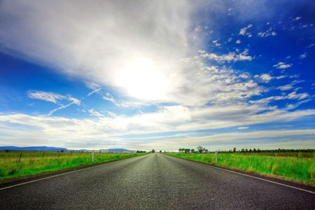 Road going straight ahead under spectacular blue cloudy sky Stock Photo