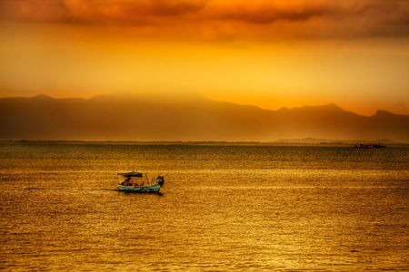 Golden asian sunset over ocean with boat Stock Photo - 2966598