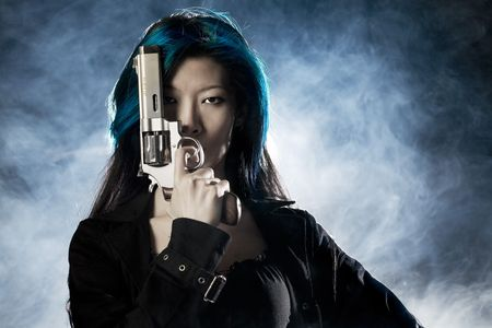 gangster girl: Asian beauty holding gun with smoke LANG_EVOIMAGES