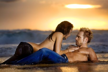 Young sexy couple on beach topless in jeans
