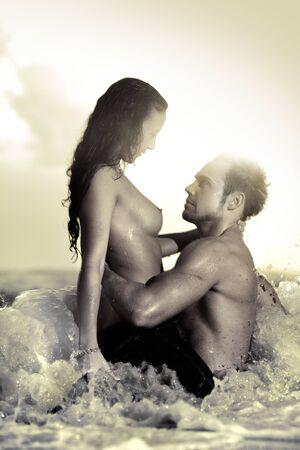 Pareja joven sexy en la playa en topless en pantalones vaqueros  Foto de archivo