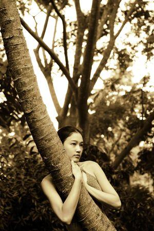 Asian girl outside hugging long thin tree photo