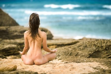 nude nature: Naked woman meditates with ocean in background