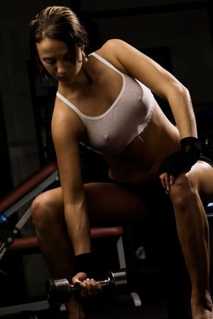 tricep: Sexy woman in gym uses weights LANG_EVOIMAGES