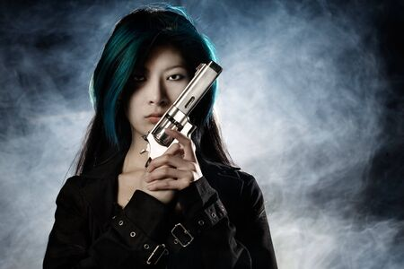 Asian beauty holding gun with smoke in background Stock Photo
