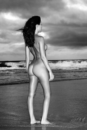 Mujer desnuda en la playa con los oc�anos en el fondo, monocromo  Foto de archivo