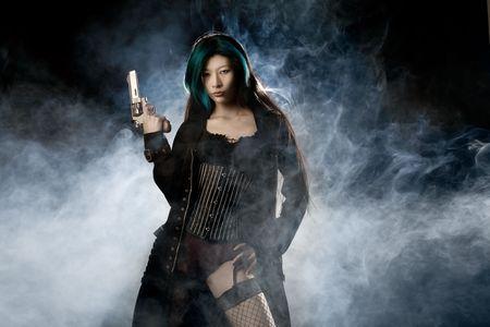hitman: Asian beauty holding gun with smoke in background Stock Photo