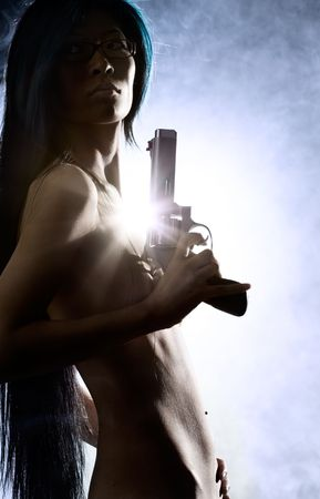 Naked beauty holding gun with smoke in background Stock Photo - 3012180