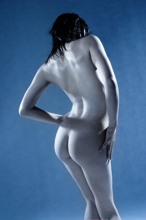 artistic nude: Artistic nude of woman in studio tinted blue Stock Photo