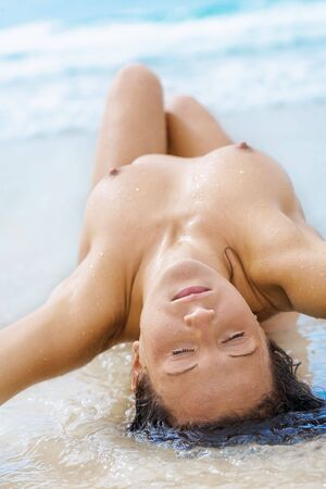 Naked woman on beach, laying down photo