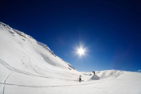 skier jumping: Alpine scenic of two snowboarders shaping a jump