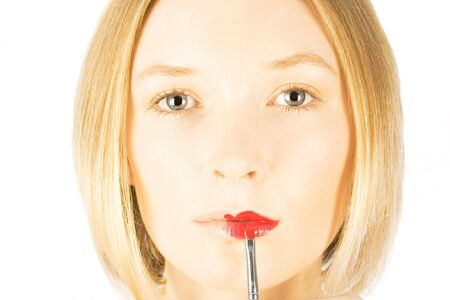 lip stick: Beautiful blonde gets lip stick applied on white studio background