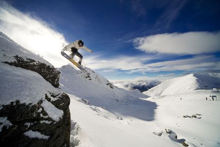 Snowboarder riding off cliff with deep blue sky in background Banco de Imagens