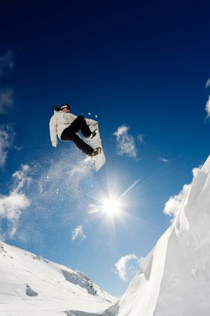 Snowboarder jumping through the air with blue sky background Stock Photo