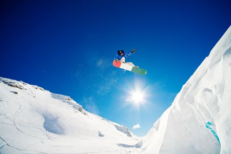 Snowboarder jumping through the air with blue sky background Banco de Imagens