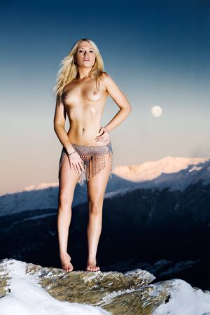 Topless model outdoor on snow covered mountain Stock Photo