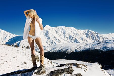 Fashion model outdoor in snow wearing white fur