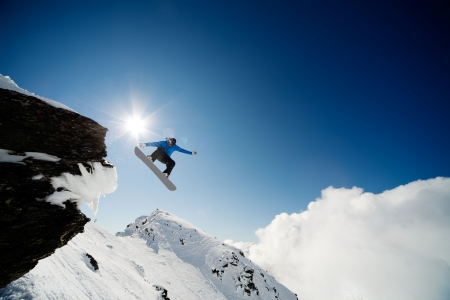 snowboarder jumping: Snowboarder jumping through air after rock drop Stock Photo