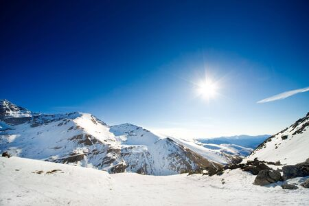 Alpine landscape of snow covered mountains and blue sky