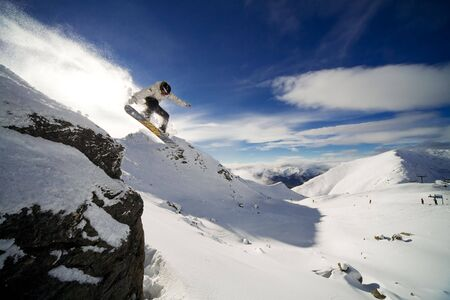 Snowboarder riding off cliff with deep blue sky in background LANG_EVOIMAGES