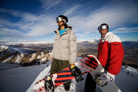 on skis: Two snowboarders stand on a peak over looking a spectacular view Stock Photo