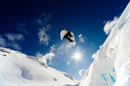 snowboarder jumping: Snowboarder jumping through the air with blue sky background Stock Photo