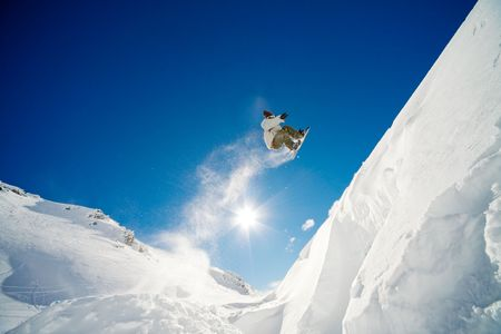 Snowboarder jumping through air with blue sky in background Stock Photo - 3690377