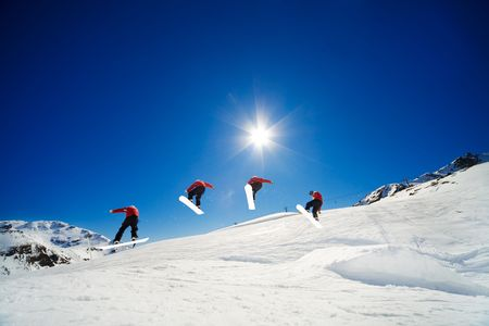 Sequence shot of snowboarder going over jump photo