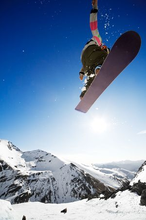 ski jump: Snowboarder jumping through air with deep blue sky in background